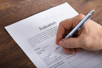"person filling out form that says ""evaluation"""