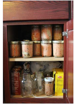 Photo of home canned foods in a cupboard.