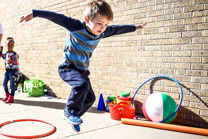 A preschooler jumping and playing with a hulahoop.