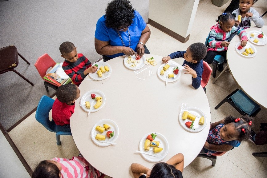 preschoolers and a teacher sharing a meal around a table