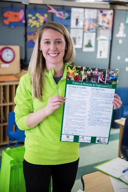 A staff member holding a wellness policy poster.