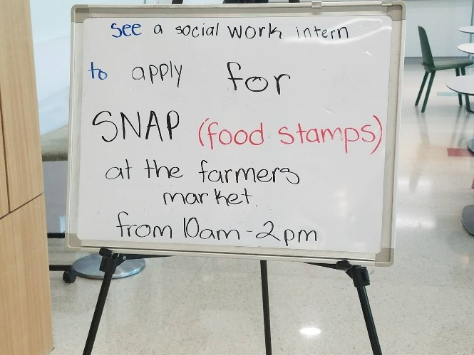 "White board with text ""See a socail work intern to apply for SNAP (Food Stamps) at the farmers market from 10am - 2pm"""