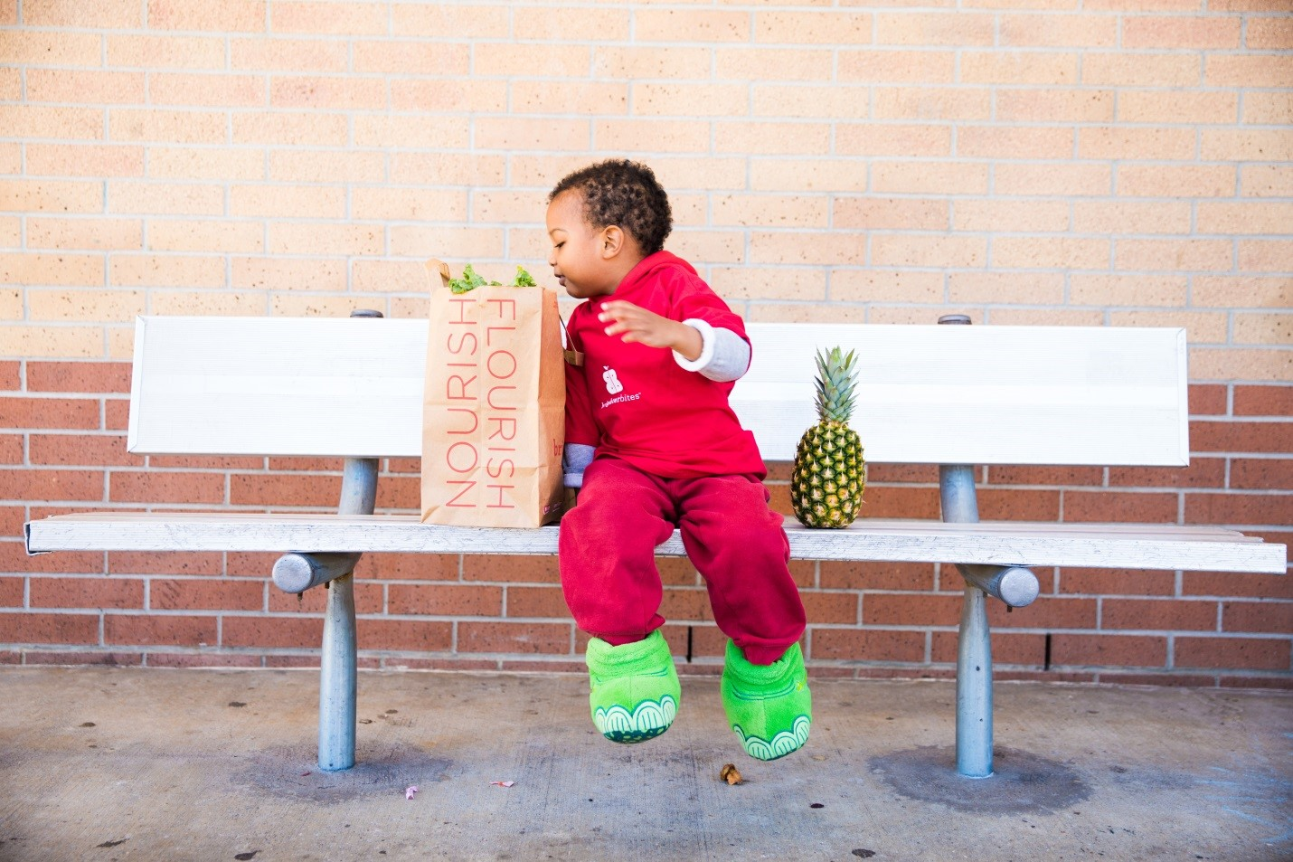 a boy sits on a bench with a bag of groceries