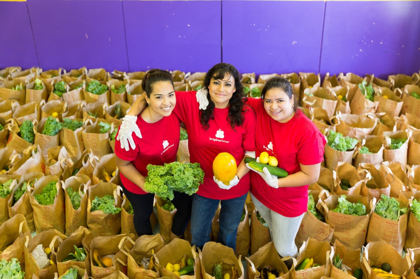 three women stand among a bunch of produce filled bags