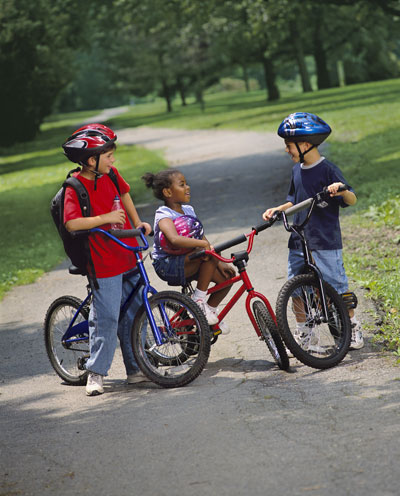 Three children taking a break during a bike ride on a paved path.