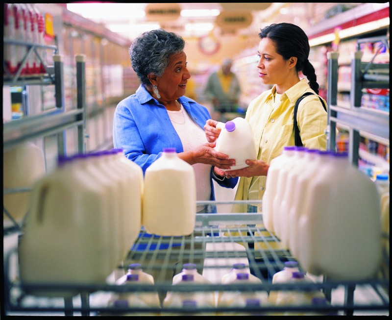 Two women in the dairy section of a grocery store looking at a gallon of milk and discussing the label