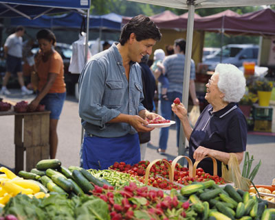 A grocer at a farmers' market offers an older woman a sample of strawberries