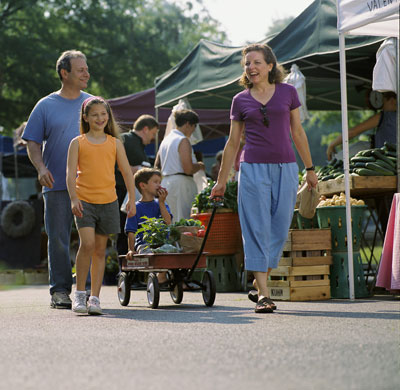 A family of four walking through a Farmers' Market, mother is pulling a red wagon.