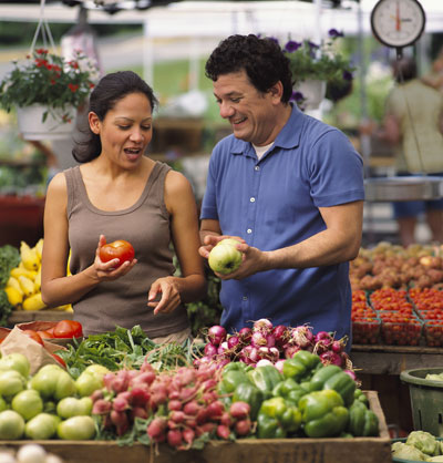 A man and woman look at produce at a farmers' market