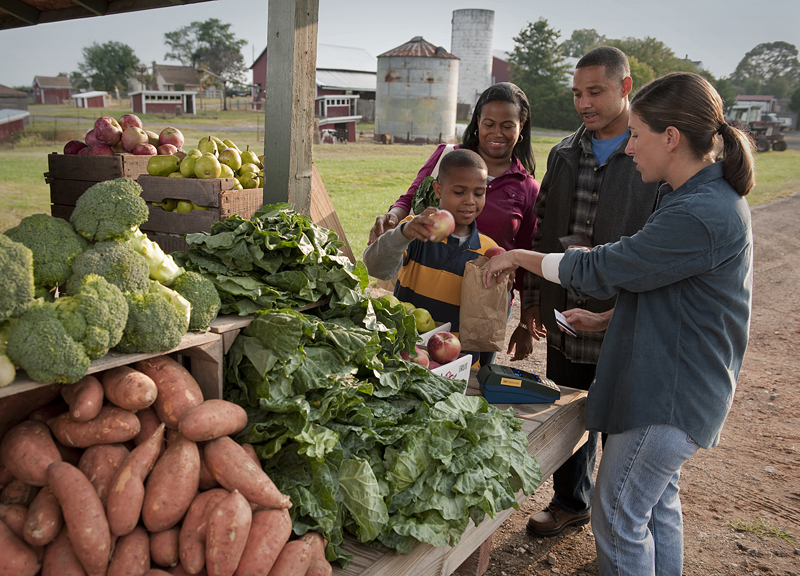 A family purchases produce from a farmers' market vendor