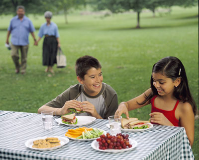 A boy and a girl talk during a picnic while grandparents walk in the background
