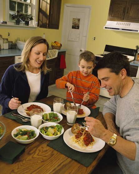 A family sits around a kitchen table and eat spaghetti for dinner