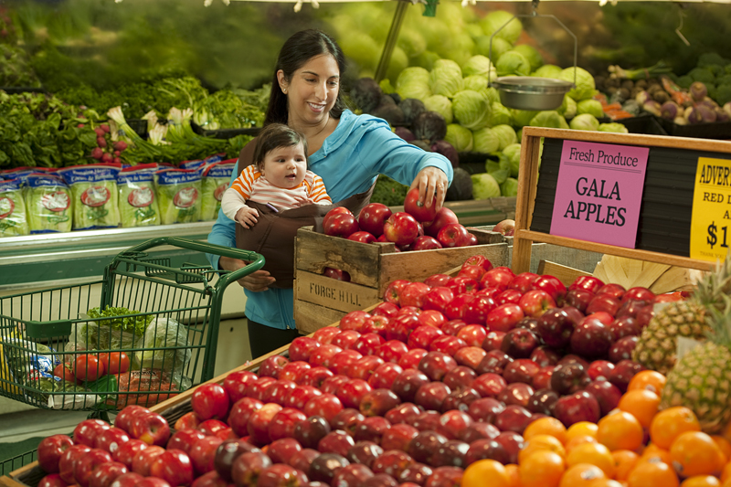 A woman and her infant shop for fruit at a grocery store