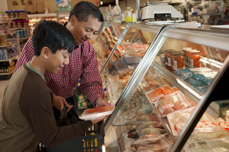 A man and his son shop for seafood at a grocery store