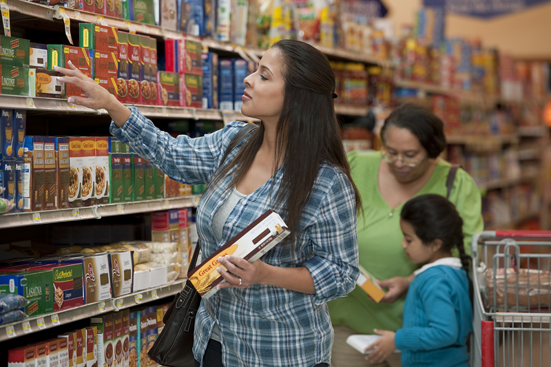 A woman, her mother and daughter at a grocery store shopping for while grain pasta and using a shopping list
