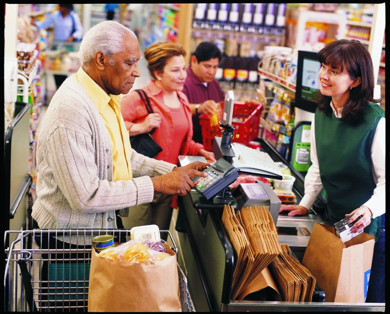 An older adult man checking out at a grocery store and paying with a credit/debit/EBT card.