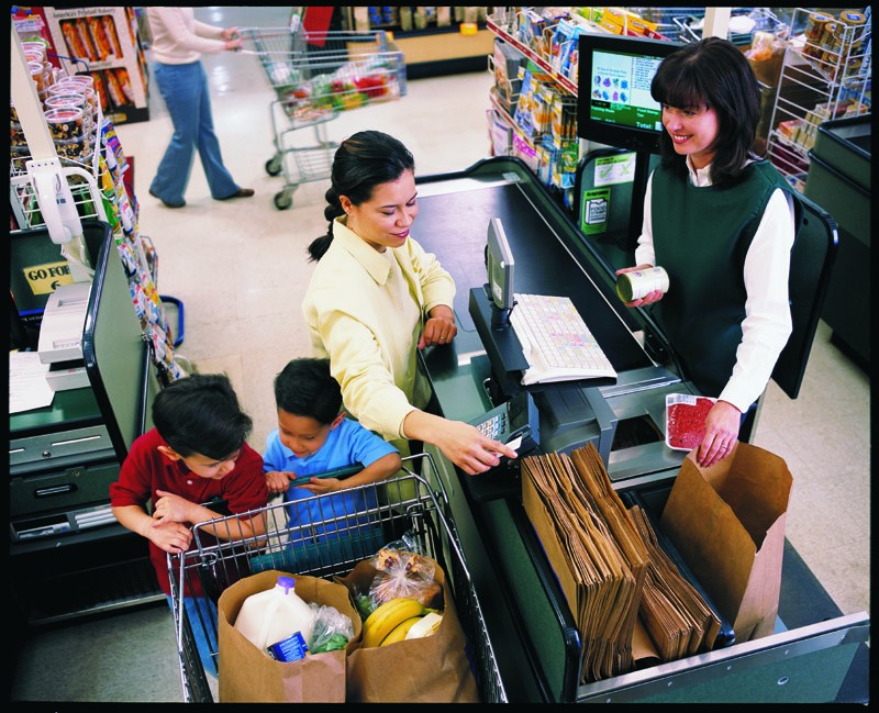 A woman with two children checking out at a grocery store and paying with a credit/debit/EBT card.