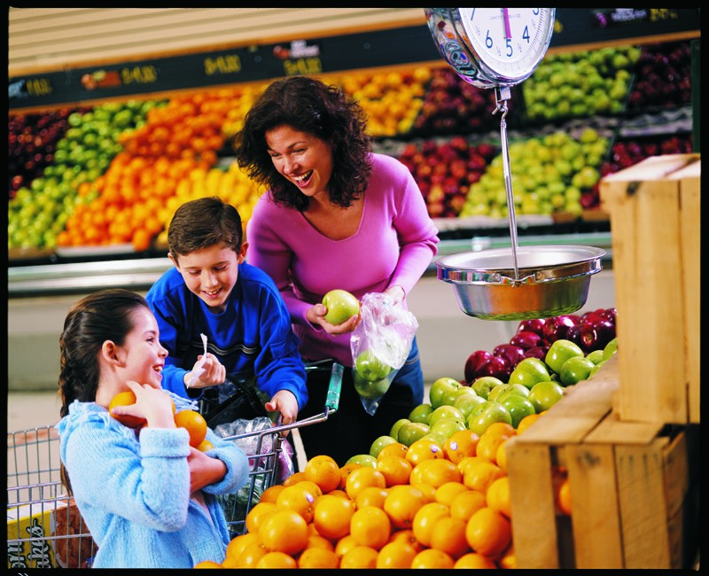 A mother with two pre-teen children selecting apples in a produce section of a grocery store.