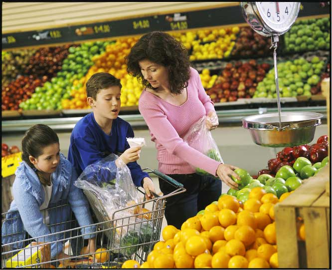 A mother with two pre-teen children using a shopping list and selecting apples in a produce section of a grocery store.
