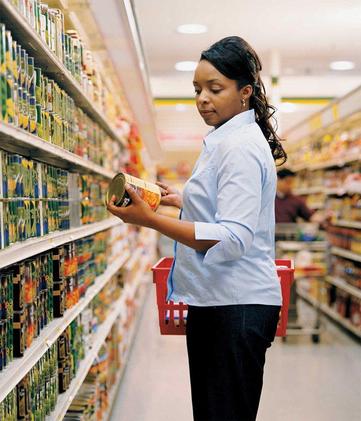 A woman looking at a can of yams in a grocery store
