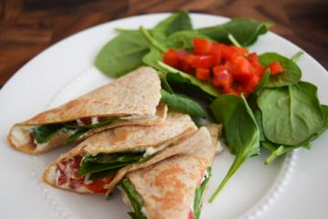 Quesadillas on a plate with spinach and red pepper