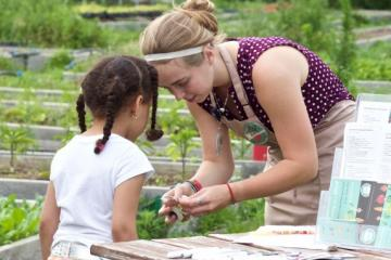 woman helping child at farmers market