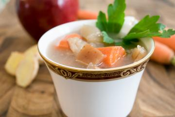 apple carrot soup in a teacup with parsley garnish