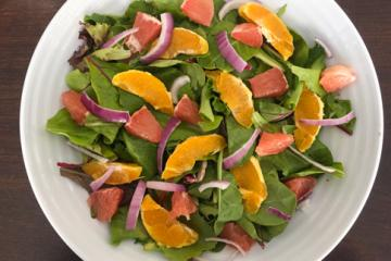oranges, red onions, and greens in a white bowl