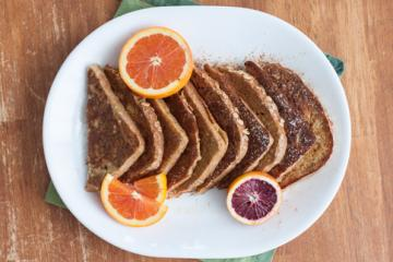French toast on a plate with orange slices