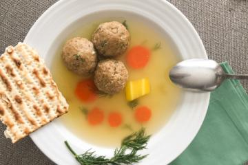 mazto ball soup in a white bowl with a spoon