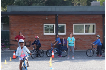 Smiling fifth-grade student at Washington STEM Elementary School riding a bicycle practicing the bike skills drills, while her classmates wait their turn to execute the course.