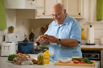 an older man makes a sandwich in his kitchen