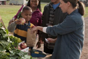 family purchasing prodice with EBT card at a farmers market