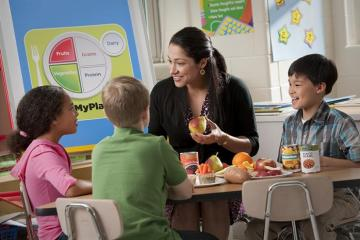 woman teaching nutrition to a group of kids
