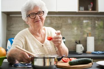 elderly woman holding a pot and a tomato.