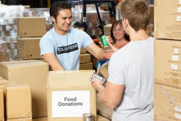 person accepting food donations at a food bank surrounded by card board boxes.