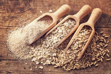 three different whole grains on a wooden background