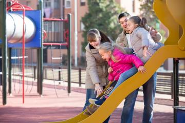 family playing with kids at an urban playground