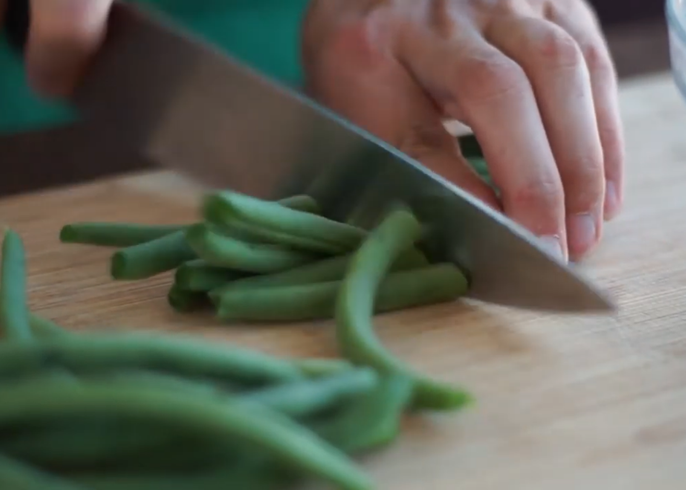 person cuts green beans with a knife