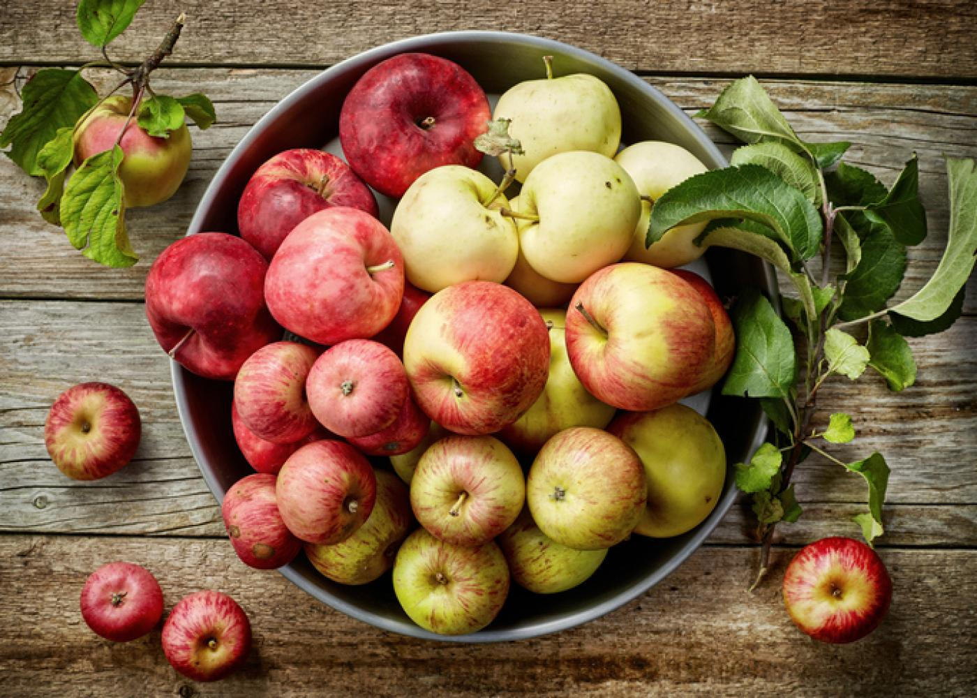 green and red apples in a bowl on a wood background
