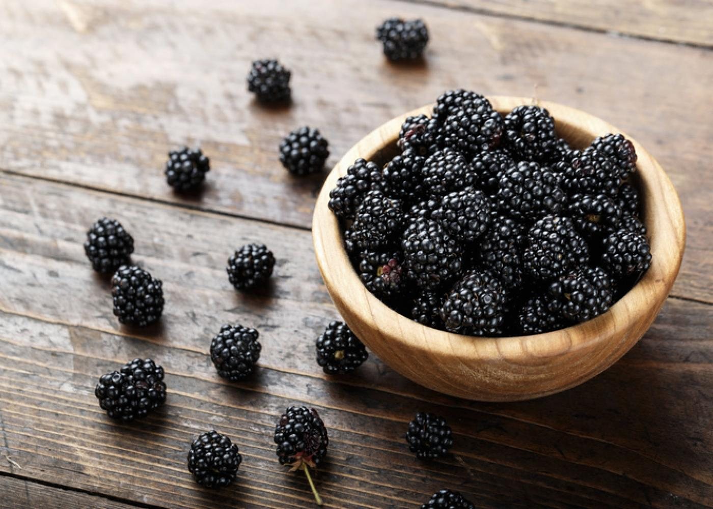 blackberries in a bowl with a few on the table next to the bowl