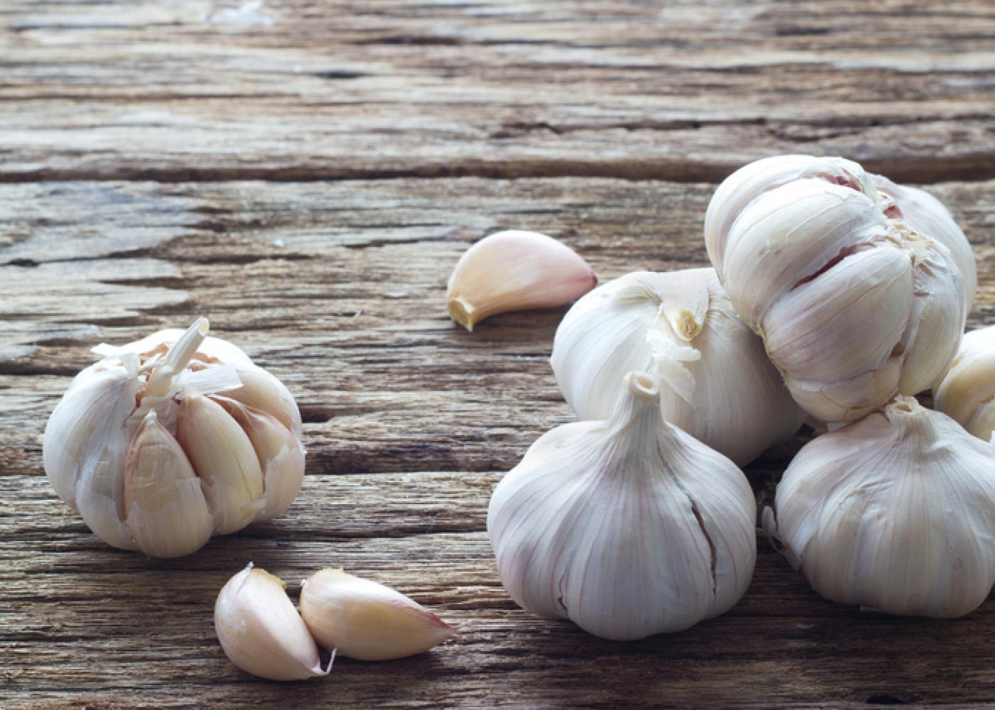 whole heads of garlic on a wood table