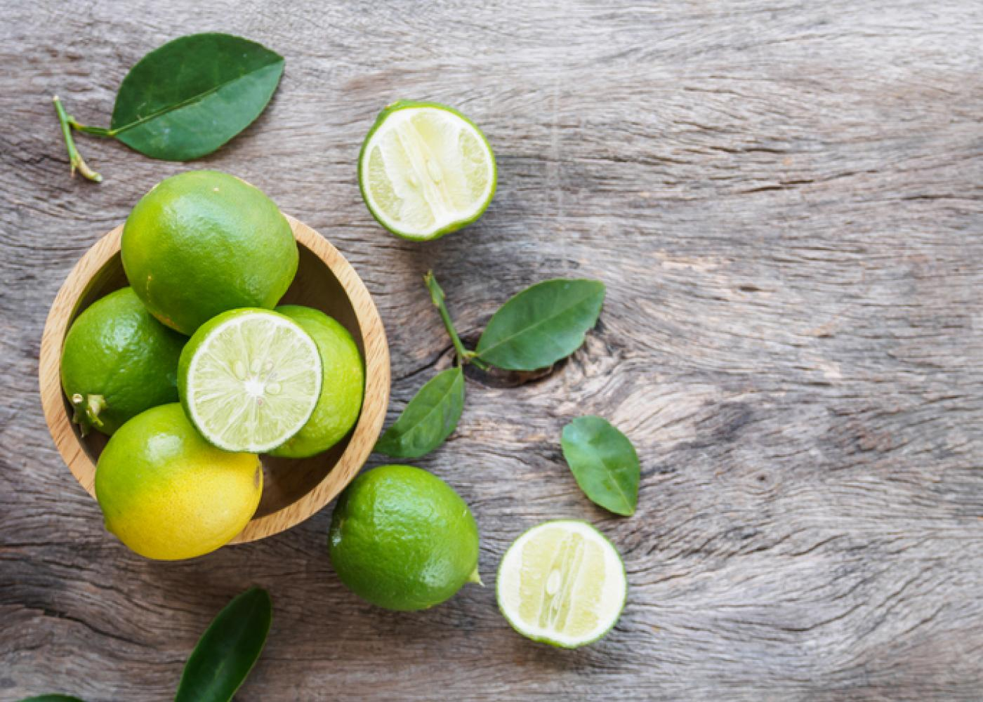 whole limes and cut limes in a basket on a table