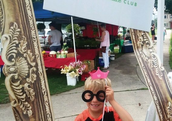 "child wearing glasses holding a sign ""POP Power of Produce Club"""