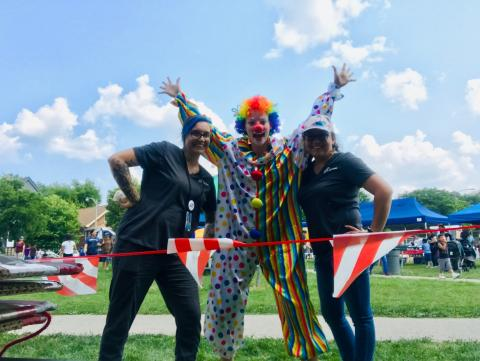 a clown poses with 2 women