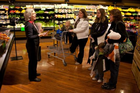 an educator talks to a group of adults in a grocery store