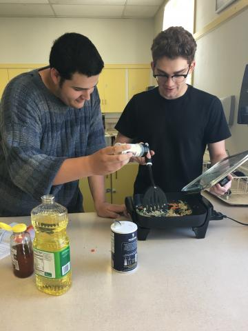 two teens cook together using an electric skillet