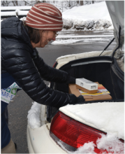 a woman get supplies out of her car