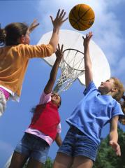 Three girls playing basketball, reaching their arms in the air for the ball