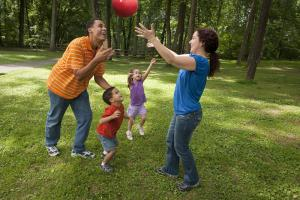 Parents with two young children play outside with a handball